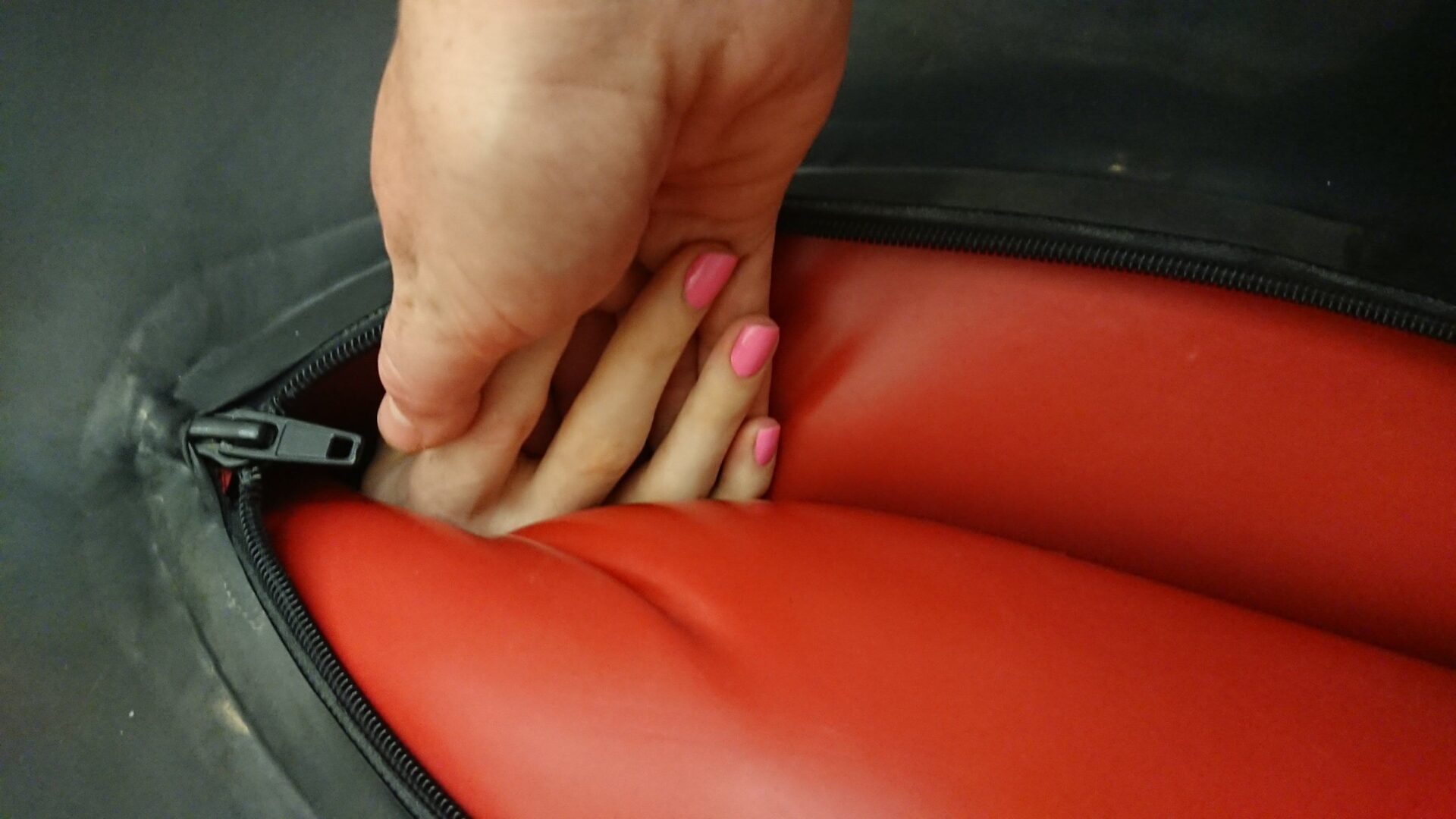 One hand with manicured pink nails reaching out from inside an inflated latex body bag., holding hands with a second hand reaching down.