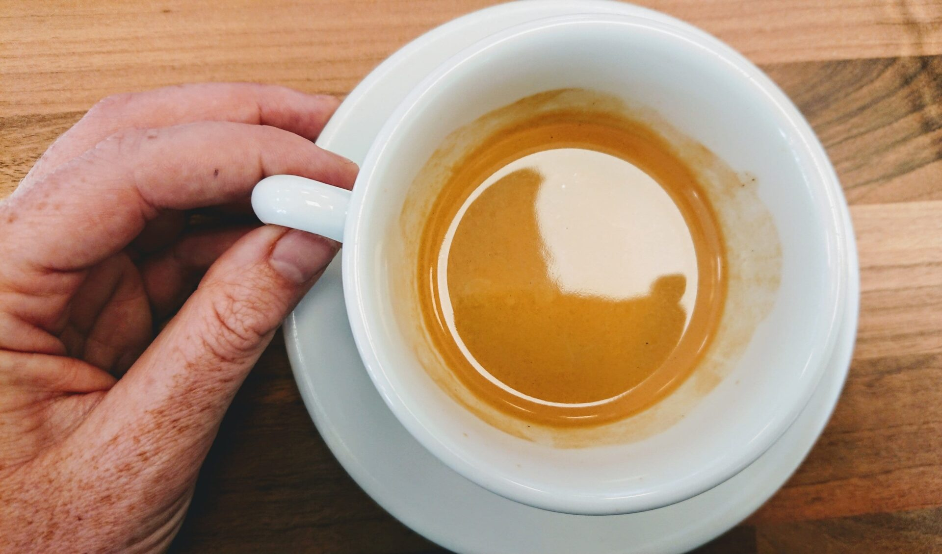 A freckled hand taking hold of an espresso cup handle, light reflecting in the glossy crema.. Featued in the post The dance we must do