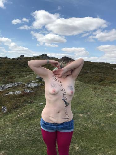 The barefoot sub on corndon tor topless with her arms crossed over her face.